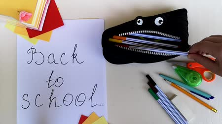 borracha : Packing a pencil case back to school, putting in it various school stuff and giving thumb-up. Time-lapse