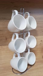 seis : Six empty large white ceramic cups hanging on stand,swaying from side to side, against the background of wooden kitchen panels. Concept of invetation for coffee. Modern design, minimalism. Vertical