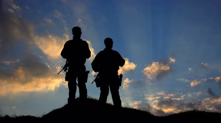 silhueta : Two Soldiers Silhouette Standing Against Clouds HD Vídeos