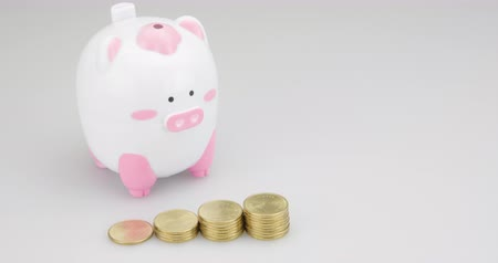completo : Step up of gold coins time lapse. Piggy coin bank on white background for money savings, financial security or personal funds concept footage.
