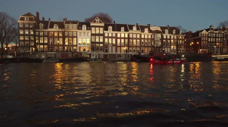 Cruising on the river Amstel in Amsterdam Netherlands at sunset