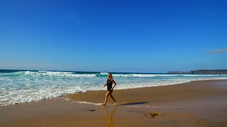 Sportive woman jogging on the beach