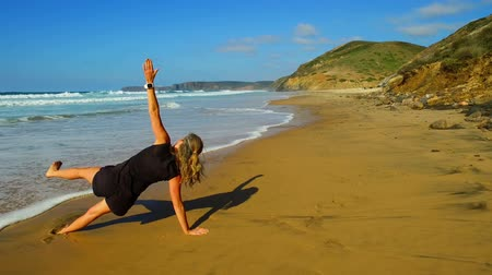 Sportive woman is doing excersises on the beach