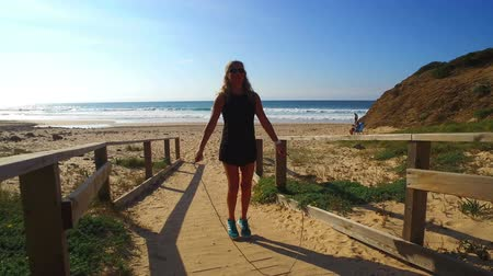 weight training : Sportive woman doing jumping rope exersises on the beach