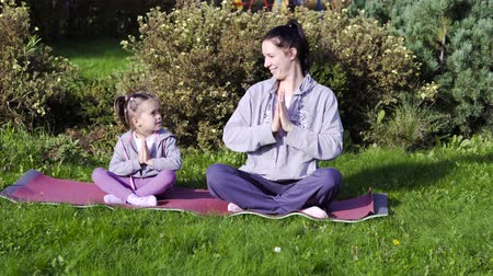 размышлять : Mother and daughter meditating together