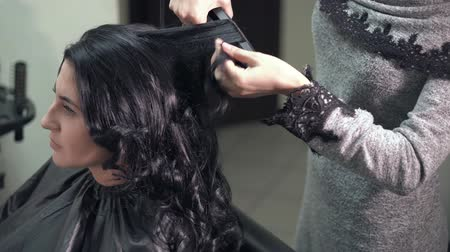 curling hair : Hairstylist curling the long black hair of a female client using a heated hair straightener