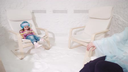 salt bed : Two women and girl relaxing in a salt cave Stock Footage