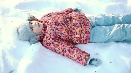 snow angel : Little girl having fun making a snow angel Stock Footage