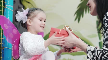 подарок : Mother gives a gift to her young daughter