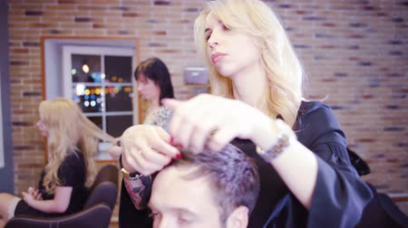 kuaför : Female hairdresser cutting hair of man client at beauty parlour