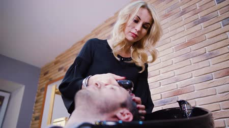 hajápoló : Professional hairdresser washing hair to her handsome client Stock mozgókép