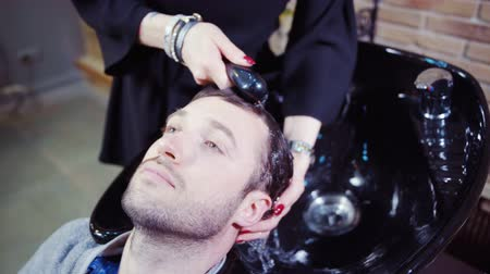 mycie rąk : Professional hairdresser washing hair to her handsome client Wideo