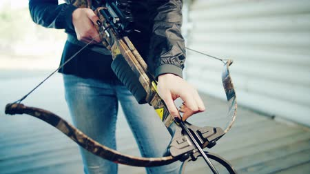 Girl inserts arrow into crossbow
