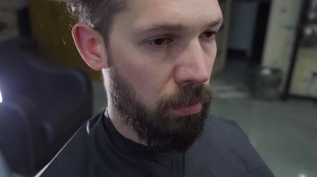A young mans hair and beard cut by scissors in barber shop.