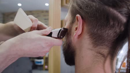 A young mans hair and beard cut by a clipper in barber shop. 動画素材