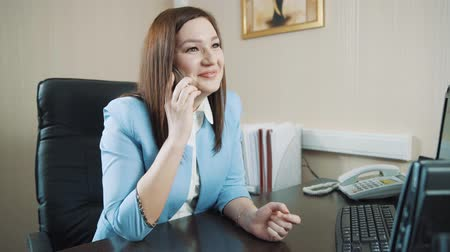 Happy brunette businesswoman in a blue jacket in the office answer phone call.