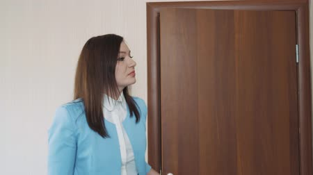 Businesswoman brunette in a blue jacket opens the door and comes into her office.