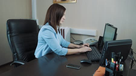 Businesswoman brunette sitting in the office and typing on the computer keyboard.