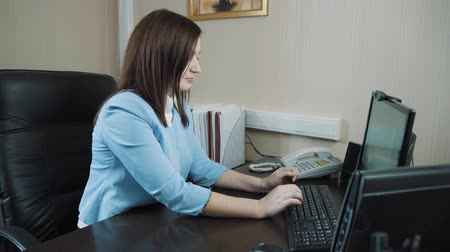 Businesswoman brunette sitting in the office andtyping on the computer keyboard. Stok Video
