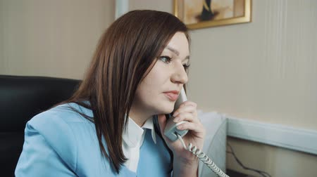 Businesswoman brunette in a blue jacket in the office talks on the phone.