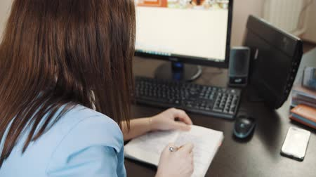 Businesswoman brunette in a blue jacket writes in her diary on the desk in the office. Stock mozgókép
