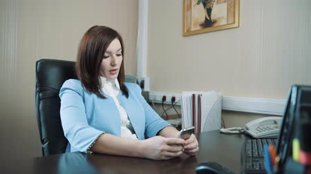 Businesswoman brunette in a blue jacket sat down in her chair in the office and started to work on the keyboard.