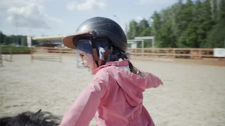 Happy little girl is riding a black pony in equestrian club. Stok Video