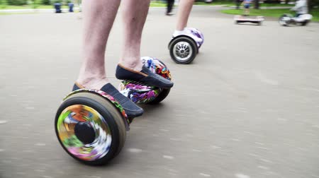 Close up of legs: a guy and a girl riding on hoverboards in the park.