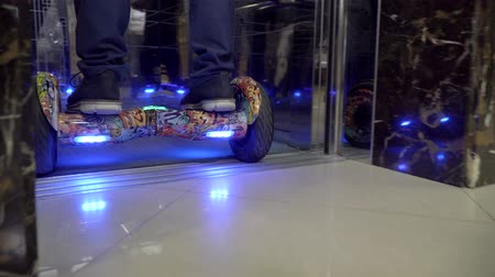 Close up of legs: a man riding on hoverboards into the elevator. Stok Video