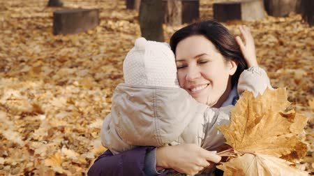 Happy woman hugging her little daughter in the autumn park. Stok Video