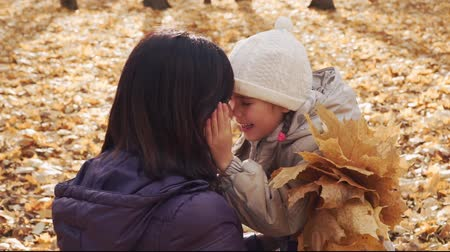 Happy little girl hugging her mother in autumn park.