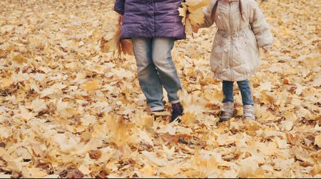 zsinórra : Happy little girl with her mother kicking autumn leaves in the park.