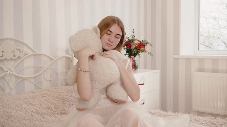 плюшевый мишка : Blonde bride in negligee looks and hugs teddy bear Стоковые видеозаписи