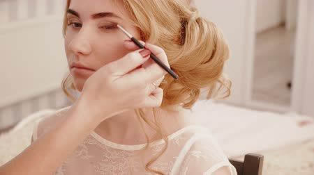 negligee : Stylist makes eyes makeup to the blonde bride girl Stock Footage