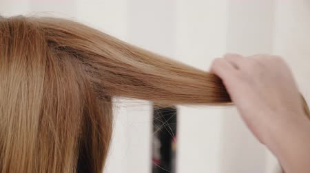 negligee : Stylist combing long hair to blonde girl