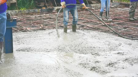 plasterer : Workers man using a Vibration Machine for eliminate bubbles in concrete. after Pouring ready-mixed concrete on steel reinforcement to make the road by mixing mobile the concrete mixer.