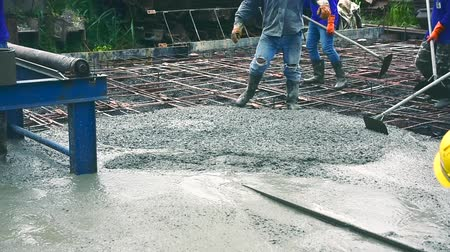 reinforced : Man using a wooden spatula for cement after Pouring ready-mixed concrete on steel reinforcement to make the road by mixing mobile the concrete mixer.