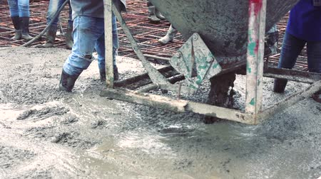 cement floor : Man worker using a concrete steel basket for cement after Pouring ready-mixed concrete on steel reinforcement to make the road by mixing mobile the concrete mixer.