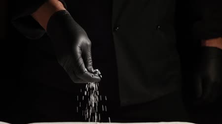 cuisine dark : black latex gloved hand sprinkles white coarse salt on black background