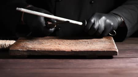 apontador : cook in black latex gloves sharpens a knife