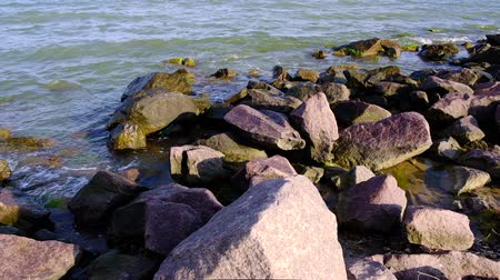 waters : Black Sea coast with large stones, waves splashing around on a sunny summer day,