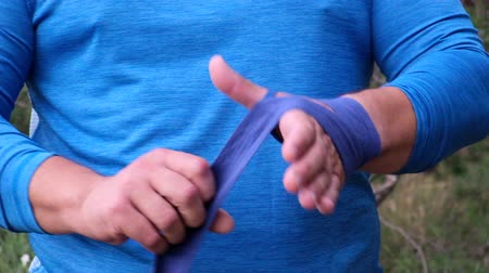 предназначенный только для мужчин : Overweight adult man in blue sportswear rewinds his hand with a blue textile bandage for sports and boxing outdoors in the park, summer day