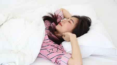 kap : Beautiful young asian woman waking up in the morning and stretching and gets up sitting on bed in the bedroom, girl sleep cozy and wake with fresh happy and smile, wellbeing and health concept.
