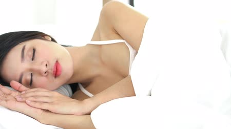 wakeup : Beautiful asian young woman sleeping lying in bed with head on pillow comfortable and happy waking up moving panning camera. girl with relax for health concept, slow motion. Stock Footage