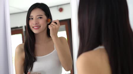 corar : Beauty portrait asian woman applying makeup with brush of cheek look at mirror indoors, beautiful girl holding blusher, skincare and cosmetic concept, slow motion.