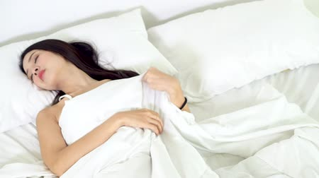 wakeup : Beautiful asian young woman sleeping lying in bed with head on pillow comfortable and happy moving panning camera. girl with relax for health concept, slow motion, top view.