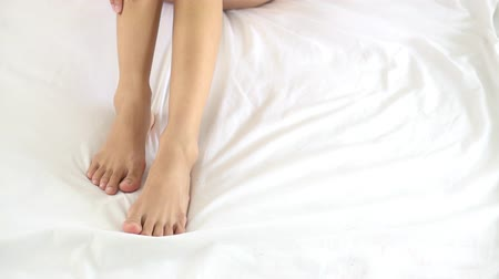 sedoso : Beautiful young asian woman touching legs soft and moisturisers on bed in the bedroom, girl massage spa, healthcare skin beauty concept. Vídeos
