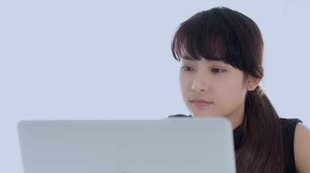 secretária : Beautiful young freelance asian woman smiling working and typing on laptop computer at desk office with professional, girl using notebook checking email or social network, business and lifestyle concept. Stock Footage