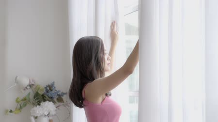 vakok : Beautiful portrait young asian woman relax open curtains at the window looking outside with hope and future in bedroom in the morning after wake up, girl with healthy happy leisure, lifestyle concept.