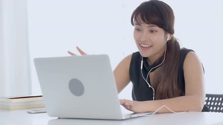 köszönt : Beautiful young asian woman smiling say hello using chat social network with video call on laptop computer, teen girl relax enjoy communication and lifestyle concept.
